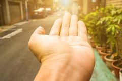 Young man`s hand, palms up to greet the sun, walking on the road while traveling. Symbol of health, lifestyle, freedom. This video expresses the relationship Stock Photo