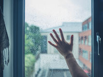 Young man's hand touching window with dew Stock Images