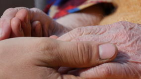 A young man`s hands comforting an elderly pair of hands of grandmother outdoor close-up.Sun comes out from behind the