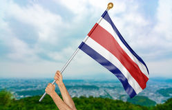 Young man`s hands proudly waving the Costa Rica national flag in the sky, part 3D rendering Royalty Free Stock Photo