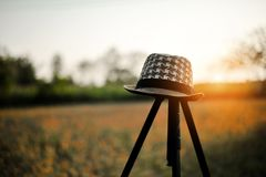 A young man`s hat is placed on a tripod. With sunset in the even royalty free stock images