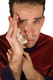Young Man's Headache. Young male with a migraine headache, close-up of his face Stock Image