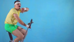 Young man from 80`s with mustache on exercise bikeon blue background showing thumb down slow mo. Funny young man from 80`s with mustache on exercise bike on blue stock video