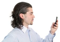 Young man's profile with phone in hand isolated. Profile of young dark haired man in light blue striped shirt with cell phone  isolated on white Stock Images