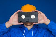 Man  in 90s sports jacket and yellow hat with VHS cassette on blue background stock image