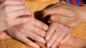 A young man`s and woman`s hands comforting a old pair of hands of grandmother outdoor. Stock Photography