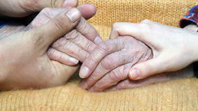 A young man`s and woman`s hands comforting a old pair of hands of grandmother outdoor. Royalty Free Stock Image