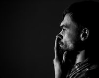 Young man, sad emotions, black and white photography. Sad young man on a dark background, sad emotions, black and white photography, close-up Royalty Free Stock Image