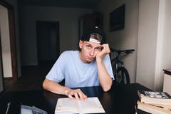 Young man with a sad facial expression reads a book in his house. Royalty Free Stock Photos