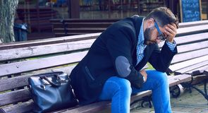 Young man with sad facial expression sitting on a bench in the park. Office worker lost his job. Middle aged man despair. Young man in glasses sitting on a bench royalty free stock photo
