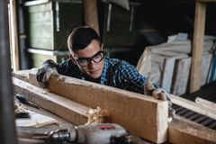 Young man in safety glasses and gloves checks the quality of the planed wooden board. Manual labor, carpenter Royalty Free Stock Image