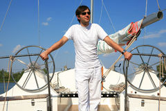 Young man on sailboat desk looks ahead. Stock Images