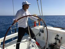 Young man sailing yacht steering wheel vacation Royalty Free Stock Photography