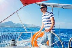 Young man sailing yacht Stock Image