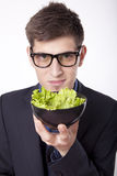 Young man with a salad. Young man looking at the salad Royalty Free Stock Photos