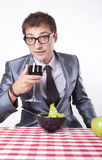 Young man with a salad. Drinking wine Stock Images