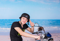 Young man saluting on his motorbike Royalty Free Stock Photos