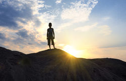 Young man in sand desert in sundown silhouette Royalty Free Stock Photo