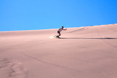 A young man on the sandboard Stock Photos