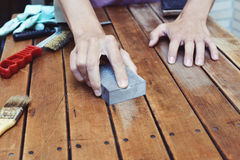 Young man sanding a wooden table with a sanding block Royalty Free Stock Images