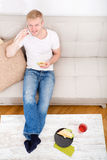 Young man with a Sandwich on the Sofa Stock Images
