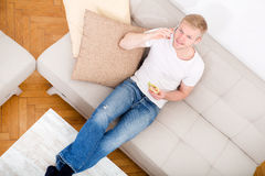 Young man with a Sandwich on the Sofa Stock Photography