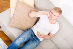Young man with a Sandwich on the Sofa Stock Photos