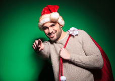 Young man in santa cap pointing to  camera Stock Photography