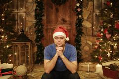 Young man in Santa Claus cap sits at home on steps of decorated christmas style Stock Photos