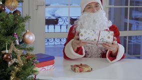 Young man in Santa Claus costume sit on the table and sign the present. Young man in Santa Claus red costume sit on the table and put signature to the one of the stock footage