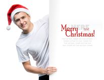 Young man in a Santa Claus hat. Cute man in a Santa Claus hat behind the white board with space for text Stock Images