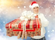 Young man in Santa Claus hat holding a gift box Royalty Free Stock Photos