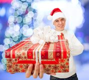 Young man in Santa Claus hat holding a gift box. Portrait of a handsome young man in Santa Claus hat holding big red gift box Stock Photo