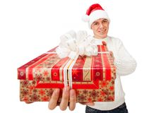 Young man in Santa Claus hat holding a gift box. Portrait of a handsome young man in Santa Claus hat holding big red gift box Royalty Free Stock Image
