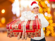 Young man in Santa Claus hat holding a gift box Royalty Free Stock Images