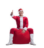 Young man santa claus sit on red bag with presents Stock Photo