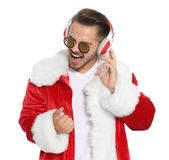 Young man in Santa costume listening to Christmas music. On white background stock images