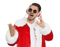Young man in Santa costume listening to Christmas music. On white background royalty free stock images