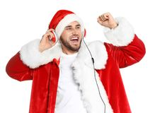 Young man in Santa costume listening to Christmas music. On white background stock image