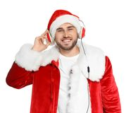 Young man in Santa costume listening to Christmas music. On white background stock photos