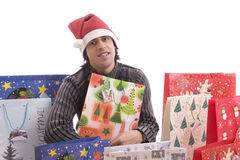 Young Man in Santa hat, full of gifts Stock Photography