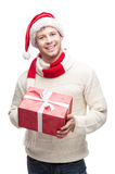Young man in santa hat holding big red christmas g. Young casual caucasian man holding big red christmas gift with nice toothy smile royalty free stock photography