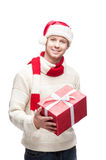 Young man in santa hat holding big red christmas g. Young casual caucasian man holding big red christmas gift with nice toothy smile royalty free stock images