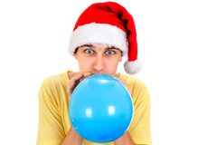 Young Man with a Balloon. Young Man in Santa Hat inflate a Blue Balloon on the White Background Stock Image