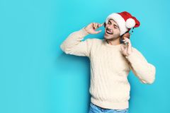 Young man in Santa hat listening to Christmas music. On color background stock photo