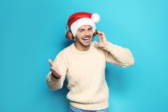 Young man in Santa hat listening to Christmas music. On color background royalty free stock image