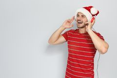 Young man in Santa hat listening to Christmas music. On color background royalty free stock photos