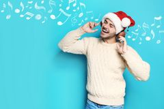 Young man in Santa hat listening to Christmas music. On color background stock image
