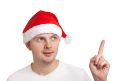 Young man in santa hat pointing up Stock Image