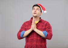 Young man in Santa hat praying Stock Photography